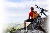 Ein Fahrradfahrer sitzt auf einem Berg und macht eine Pause
